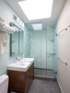 A large skylight brightens up this modern bathroom, reflecting off of the white walls. The double vanity looks modern and pristine, and the walk-in shower with clear glass visually expands the space.