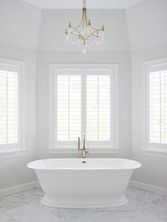 Glamorous Large White Marble Master Bath with Freestanding Victoria and Albert Tub and Rohl fixtures. Designed by SHOPHOUSE Interior Designers. Bay window with plantation shutters and Currey Chandelier over tub. www.shophousedesign.com