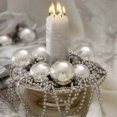 Fill a silver bowl with shining beads, a pillar candle and several medium-sized glass balls. by FATIMA CACIQUE