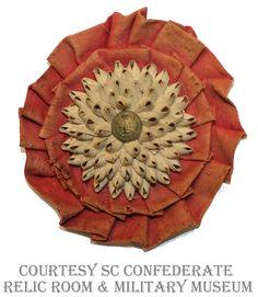South Carolina secession cockade. Red folded ribbon and palmetto sewn onto paper with a SC button. SC Confederate Relic Room & Military Museum.
