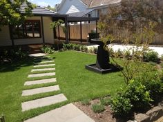 Natural bluestone stepping stones in lawn adds a soft touch to this pretty 1950's bungalow. www.desiredlandscapes.com.au