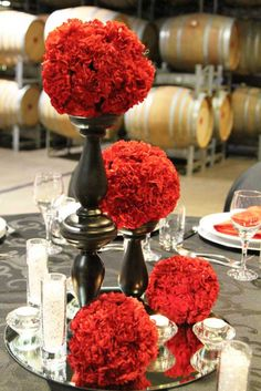 Carnation pomanders on black candlestick bases, mirror and votives. The more pomanders, the higher the cost. They are also more expensive if they're larger. Cost is going to range from $36.00-$65.00
