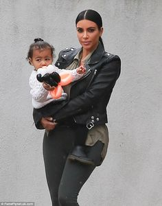 Mother love: Kim also carried the one-year-old as they dodged the rain in Los Angeles
