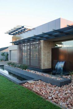 casa moderna con fuente cascada en el jardin