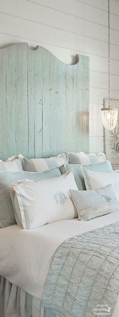 Very pale mint [green-blue] and white bedding; headboard height is exaggerated in height, also pale mint, and suggests a farmhouse/cottage setting.