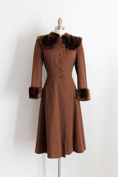 Absolutely stunning brown wool coat from the 1940s. This jacket features a flattering silhouette, buttons up the front, and a fur collar and