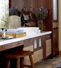 The clean lines of this stylish bowl-style sink complement the organic feel of this bathroom. The natural beauty of wood takes center stage on vanity cabinet doors and walls.