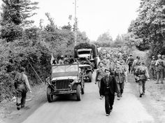 American troops moving up to the front lines, right, pass a long line of German prisoners marching back to a holding camp prior to being shipped out of France, on June 12, 1944. (AP Photo)