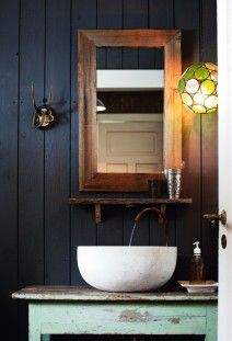dark blue wall, wood frame, cool sink and table