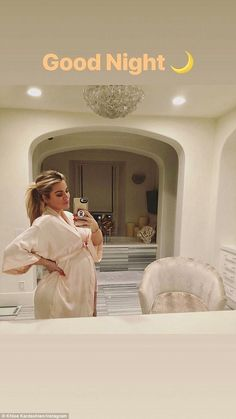 Oh baby: Khloe Kardashian highlights her growing bump as she poses in a robe on Sunday