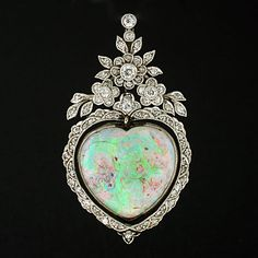 A stunning opal pendant from the Art Nouveau (1910) era! This delicate piece depicts a large, heart shaped opal which is surrounded by sparkling diamonds. The opal, which is vibrant in color with hues of green, pink, purple, blue and yellow, is bezel set in an 18kt white gold setting. An ornate diamond encrusted frame surrounds the opal heart and an intricate diamond encrusted floral topper rests at the top of the piece. [Except it's more Garland style than Art Nouveau]