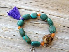 """TIGER EYE BUDDHA BRACELET tiger eye buddha is sure to bring good luck and good fortune. Tumbled turquoise and faceted carnelian encompass a craved tiger eye, smiling buddha. Stretch bracelet measures 7"""", sized to fit most wrists."""