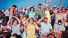 Arms up to protect eyes from the sun. These people are watching the launch of Apollo.