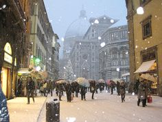 Florence, Italy in winter. Chunks of snow fall as the Duomo peeks through the tightly woven buildings lining the street