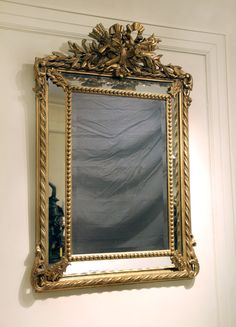 The top centered by 2 birds perched on acanthus leaves, with a torch crossed with a quiver of arrows, topped by a bow.  Twisted carved rope designs make up the outside of the frame.