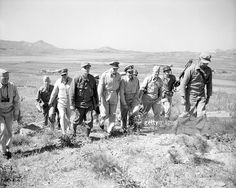 General Douglas MacArthur and staff walk up a hill to see over the front line during the Korean war, 1950.