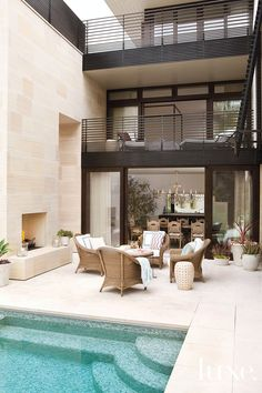 The house was designed to blur the lines between indoors and out. Here, Restoration Hardware lounge chairs surround a fireplace in an outdoor conversation area that lies between the formal dining room and the pool. The coffee table was found at Inner Gardens.  What is the mosaic pool tile!!! Gorgeous :)  And stone fireplace paver...TDF
