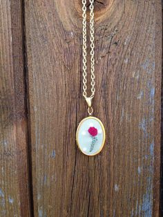 "A small, simple, hand embroidered necklace featuring a lovely dark pink rose.    - Lead and nickel free!  - This oval setting is gold tone and 2"" x a little over 1"" or 38mm x 28mm in size diameter - slightly larger than a quarter.  - Chain (gold setting) is about 18"" with clasp."