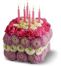 "Wish someone many more years of health and happiness – send them this endearing ""cake"" created with fresh flowers in pretty hues of pink, lavender and white, and topped with six real birthday candles! A unique and charming way to celebrate a birthday.    A pave arrangement of fresh flowers such as chrysanthemums and miniature carnations in shades of hot pink, white and lavender is designed into the shape of a cake, and topped with six pink birthday candles."