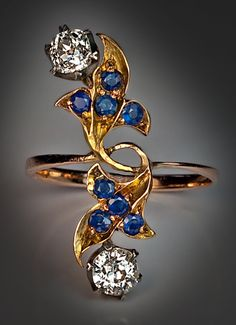 An Art Nouveau Diamond and Sapphire Floral Ring    This elegant gemstone Art Nouveau ring was handcrafted in Moscow between 1908 and 1917.    The ring is vertically set with two interlaced stylized flowers   embellished with two old cut diamonds (approximately 0.50 ct and 0.60 ct) in silver prong settings and eight round faceted blue sapphires.