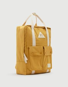 Mustard yellow fabric backpack with front pockets, a zip closure, a handle, adjustable shoulder straps and an inside pocket. Yellow Backpack, Backpack Outfit, Backpack Bags, Pull & Bear, Casual Bags, Herschel Heritage Backpack, School Backpacks, Mustard Yellow, Small Bags