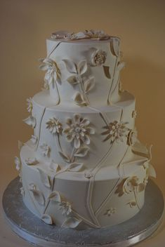 """This cake is iced all in buttercream with fondant flowers/vines.  I """"caulked"""" the tiers so that there is no borders to give it a very clean look.   I used a ball tool and foam pad to give the flower more dimension."""