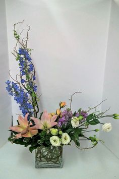 Pastel garden floral.  Incredible mix of light blues, light pink, soft purple, and white. light blue delphinium, light pink asiatic lily, white lisianthus, purple stock, peach spray rose.  spring flower arrangement