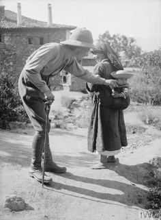 A British officer speaking to a small child which is being carried in a sling at its mother's back. Balkan Front, August, 1916. CREATOR:Varges, Ariel. Imperial War Museum Present Day, British, Museum, War, Children, Ariel, Mothers, Young Children, Boys