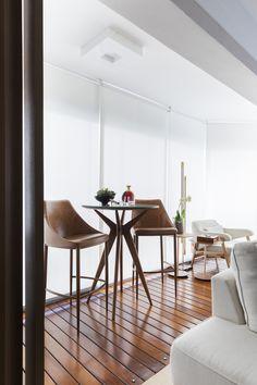 A luz natural banha todos os ambientes por consequência da integração com o terraço, que possui piso de madeira de demolição e poltronas seguindo a mesma paleta de cores neutras do living sofisticado.