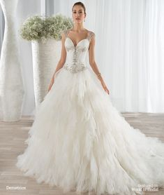 This unique ball gown features a ruffled beaded tulle skirt, beaded bodice with a sweetheart neckline and Basque waist. The sheer beaded cap sleeve transitions to a sheer open back embellished with button closures. The back features a Chapel train.