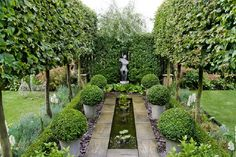 Formal garden with pleached Carpinus betulus (hornbeam) allee, Buxus sempervirens (box) balls, rill, focal point sculpture, Pyrus salicifoli...