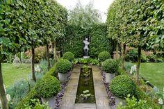 Formal garden with pleached Carpinus betulus (hornbeam) allee, Buxus sempervirens (box) balls, rill, focal point sculpture, Pyrus salicifoli...