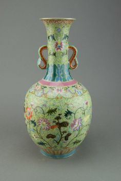 Chinese Famille Rose Lotus Vase of ovoid form with scepter shaped handles; finely painted with lotus and sprigs on light green ground between plantain leaves and ruyi heads scrolls; base marked Daoguang; H: 32 cm, D: 15 cm