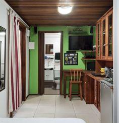 """Casa montada em um contêiner: -A única divisória, que isola o banheiro da casa contêiner, é de drywall, pintada com o mesmo verde da fachada. O banheiro (1,20 x 2 m) foi montado em um só dia: composto de seis partes, o kit pré-fabricado veio com paredes, teto e piso de fibra de vidro, além de caixas de luz e tubulação. """"Mas também é possível fazê-lo da maneira tradicional – sugiro o uso de placas cimentícias em piso e paredes, para então assentar o revestimento cerâmico"""", diz o arquiteto"""