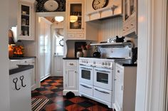Painted floors. Painted floors have a distinct country look, especially when executed in the checkerboard style shown here, offering the warmth of wood with an extra splash of color. The checkerboard creates more visual interest in a black and white kitchen than a solid wood tone would.