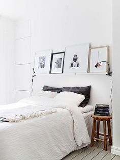 minimalist white, black, gray bedroom with light wood floors and white walls