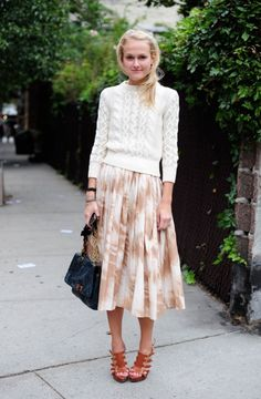The perfect way to mix summer pieces into your autumn wardrobe: Pairing floral midi skirt and sandals with a shrunken cable-knit sweater.