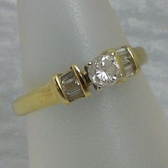 .25 Carat Round Cut Diamond Engagement Ring with Baguette Accent Diamonds set in 14k Yellow Gold. $600