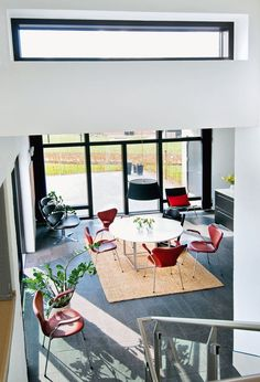 Dining area in red, white and black with Danish design - The dining table is a re-launch of a Poul Kjærholm Designs, PK 58, with the table top in Corian tree, and the chairs are Arne Jacobsens well known 'Sevens'. In the corner is a 'Corona' chair designed by Poul Volther and Poul Kjærholm's PK22 turned the back to the terrace.