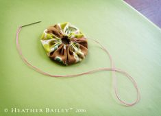 If you think you can't sew, try making yo-yos. I've been making them longer than this woman has been alive.....but she has a wonderful tutorial on how to. She also has creative fabrics, a web store and much more. Enjoy it all....~~Cyn.