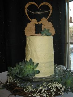 Wedding cake for an outdoorsy couple. The topper is made of wood. The bride and groom's names are engraved on the heart at the top.