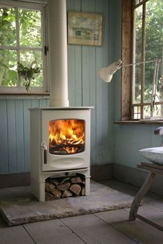 This small, white wood-burning stove has some nifty features. For one, the throat plate allows the chimney to be swept through the stove. Also, it looks great. | Tiny Homes