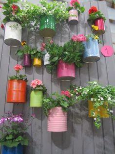 Deze geverfde potten worden op een vrolijke wijze gebruikt om de schutting te verfraaien.