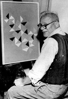 """O artista plástico Alfredo Volpi ao lado de um de seus quadros, """"Um Papagaio de Papel"""", em junho de 1956"""