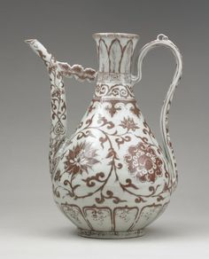 Image gallery: ewer Porcelain ewer of yuhuchun form, with high strap handle and long spout attached by a cloud-shaped strut to the neck. Underglaze red with scrolling flowers around body. Bands of squared spirals, overlapping leaves and classic scrolls on neck. Ming Dynasty Hongwu period. The British Museum.
