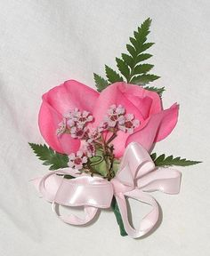 corsage featuring pink roses and pink wax flower