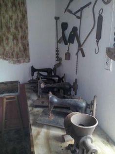 Destacan antiguas máquinas de coser, así como colgado del lado derecho sobre el muro, una antigua pesa manual.