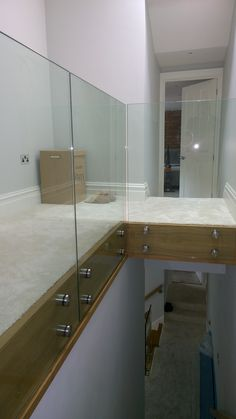 Frameless glass railings to gallery landing. Toughened and laminated clear glass panels with patch fixings side mounted.