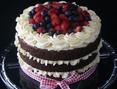 Red velvet cake with cream cheese frosting topped with fresh berries