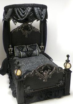 Gothic inspired dollhouse bed. Heavy textured posts,  spooky gargoyles and faces, sheer black drapes and ruffle..   www.ruthellens.faithweb.com